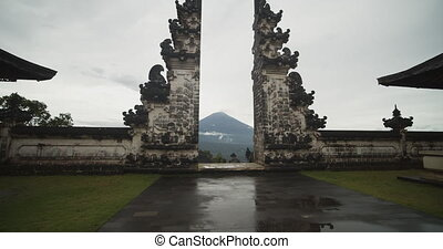 Tilting dolly shot closing in on the gates of Heaven in Pura Penataran Agung Lempuyang temple in Bali. Famous tourist attraction temple gates with Mount Agung volcano in the background. 4K