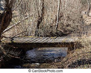 Timber bridge over little creek in springtime