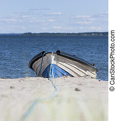 Timber rowboat on sand