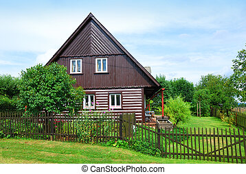 Timbered countryside house with a green backyard