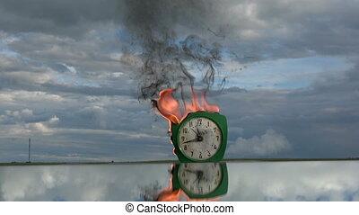 Burning old retro green alarm clock on mirror in space
