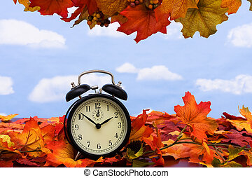 Time change - Fall coloured leaves with a black clock on a...