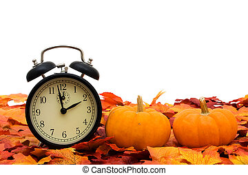 Time change - Fall coloured leaves with a pumpkin isolated...