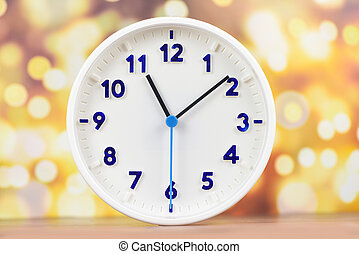 time concept / clock wall on wooden table and bokeh background white round clock