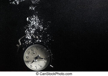 Time concept - Concept of time. Vintage alarm clock in water...