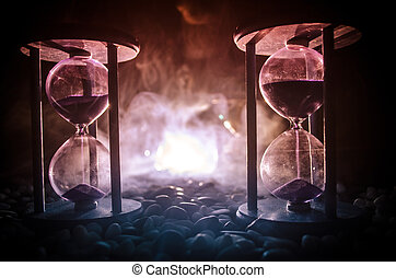 Time concept. Sand passing through the glass bulbs of an hourglass measuring the passing time as it counts down to a deadline. Silhouette of Hourglasses in smoke on dark background. With flowers