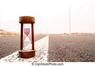 Time Concept Alarm Hourglass on the Asphalt Street