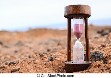 Time Concept Hourglass on the Rock Desert