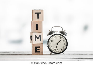 Time concept with a clock and a word on a wooden table