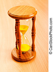 Time concept with hourglass on wooden background