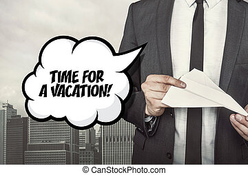 Time for a vacation text on speech bubble with businessman holding paper plane in hand