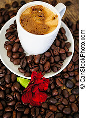 Time for coffee - Cup of coffee and red cloves flowers in a...