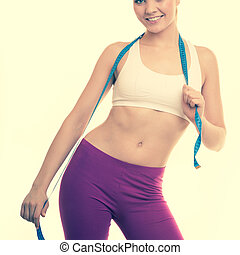Time for diet weight loss. Fit girl with measure tape.