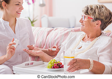 Time for dose of vitamins - Senior woman taking her pills...