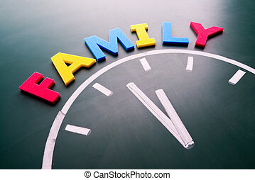 Time for family concept, color word and clock on blackboard