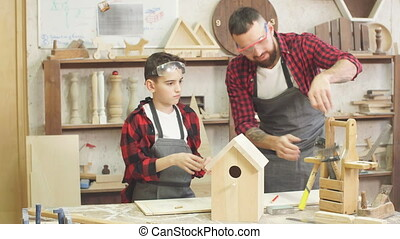 Dad shows his little son how to make birdhouse - Time for...