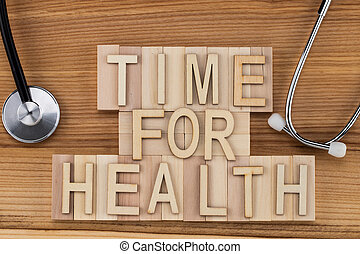 time for health -  text in vintage letters on wooden blocks with stethoscope . Medicine concept