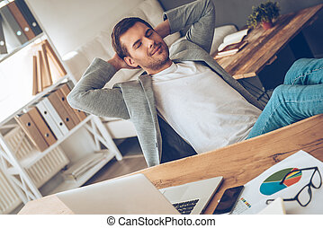 Time for little rest. Cheerful young handsome man keeping hands behind his head and eyes closed with smile while sitting at his working place