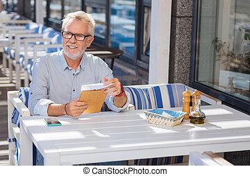 Nice elderly man sitting in the restaurant