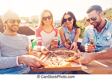 Time for pizza! Four young cheerful people eating pizza and drinking beer while sitting at the bean bags on the roof of the building