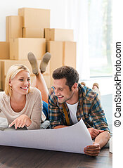 Time for planning their new house. Happy young couple laying on the floor of their new apartment and looking through blueprint while cardboard boxes laying in the background