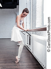 Beautiful young ballerina standing near the barre