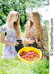 time for strawberry: 2 young beautiful brunette & blond young women girl friends having fun harvested strawberries on summer green outdoors background picture