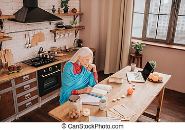Grey-haired beautiful elderly lady in blue shawl sitting at the table