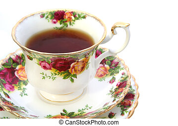 Tea in a classic gold-rimmed floral china teacup, with saucer and plate. Isolated on white.