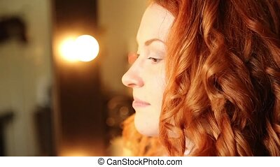 time in a beauty salon. redhead young woman in a beauty salon. Stylist makes makeup bride on the wedding day. cosmetic powder brush for make up.