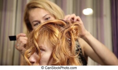 time in a beauty salon. Young woman in a beauty salon, hairdresser doing hairstyle with curls to beautiful model