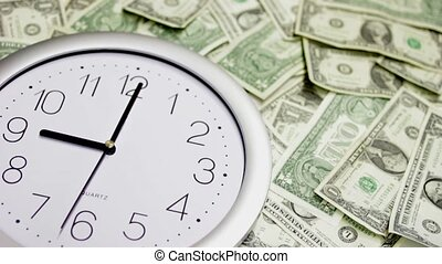 Time is Money - Clock among pile of dollars as a symbol of...