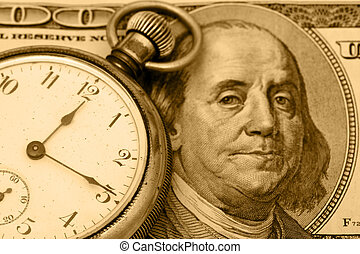 Time is Money - A stopwatch sitting on one hundred dollar...
