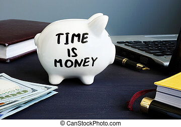 Time is money. Piggy bank at the office workplace.