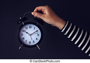Time is passing, female hand with vintage alarm clock