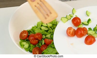 Time lapse as a woman in the kitchen preparing a salad of fresh ripe vegetables.