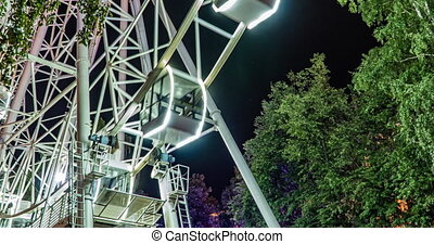 time lapse brightly lit ferris wheel ride spinning at night at a carnival, amusement park, theme park, fair, thrill park 4k