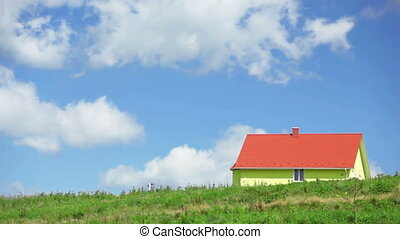 Time-lapse cumulus clouds passing over yellow small house on the hill