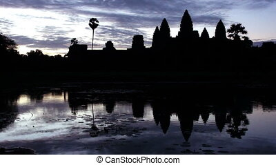 Time lapse evening silhouette shot of Angkor Wat with water reflection.