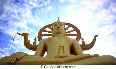 Time lapse golden Buddha statue against blue sky with moving...