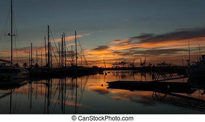 time-lapse harbor Twilight docked sailboats and cargo port cranes