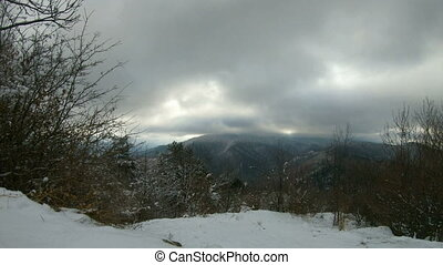 Time lapse in a winter cloudy day - Winter landscape in...