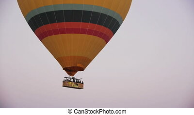 Time-lapse of a big colorful hot air balloon flying over valleys in Goreme, Cappadocia, Turkey.