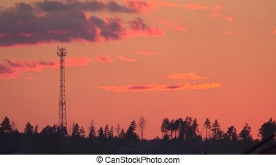 Time lapse of a cell tower silhouette against evening sky -...