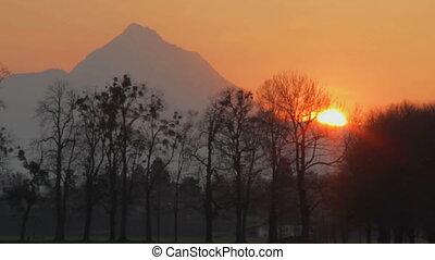 Time-lapse of amazing sunset behind mountain, beautiful nature