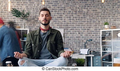 Time-lapse of bearded man resting at work sitting in lotus pose on desk relaxing