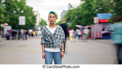 Time lapse of beautiful Asian teen with dyed hair looking at...