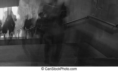 Time Lapse of black and white pictures of walking people on the stairs. Camera moving.