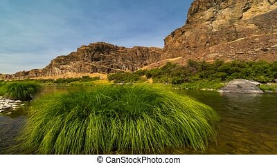 Time lapse of blue sky and beautiful green grass along...