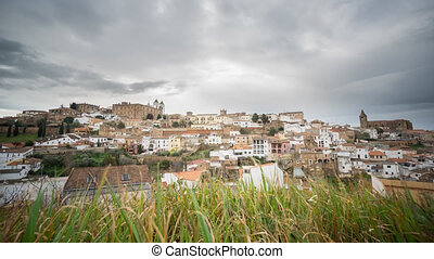 Time Lapse of Caceres, cloudy sky, grass in the foreground
